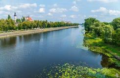 Ένας καθαρός, βαθύς ποταμός με το τύλιγμα των τραπεζών που περπατούν μετά από έναν ναό με το μαύρο θόλο Στοκ Φωτογραφίες