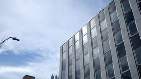Ένας καθιερώνοντας εξωτερικός πυροβολισμός ενός γκρίζου κτιρίου γραφείων χρωμίου τη θερινή ημέρα απόθεμα βίντεο