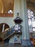 Ένας καθολικός ναός από μέσα μεγάλα Windows Ένα άγαλμα ενός αγγέλου Σημαίες με τα κεντημένα εικονίδια Στοκ Φωτογραφίες
