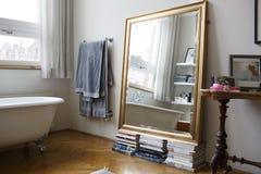 Ένας καθρέφτης στους σωρούς των βιβλίων σε ένα λουτρό Στοκ εικόνες με δικαίωμα ελεύθερης χρήσης