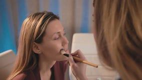 Ένας καλλιτέχνης σύνθεσης βάζει σε ένα ίδρυμα με μια βούρτσα στο πρόσωπο ενός καυκάσιου ξανθού προτύπου Επιχειρησιακή γυναίκα Mak απόθεμα βίντεο