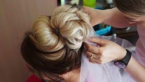 Ένας καλλιτέχνης makeup συνδέει ένα πέπλο με τη νύφη απόθεμα βίντεο
