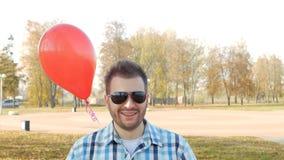 Ένας καλός μοντέρνος νεαρός άνδρας στα μαύρα γυαλιά στέκεται με ένα κόκκινο μπαλόνι και τα χαμόγελα, μια εορταστική έκπληξη, σε α φιλμ μικρού μήκους