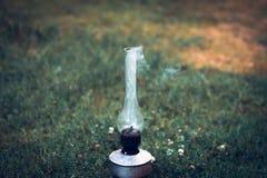 Ένας καπνίζοντας παλαιός λαμπτήρας κηροζίνης σε μια πράσινη χλόη Στοκ Φωτογραφία