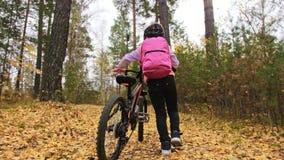 Ένας καυκάσιος περίπατος παιδιών με το ποδήλατο στο πάρκο φθινοπώρου Το μικρό κορίτσι που περπατά το μαύρο πορτοκαλή κύκλο στο δα απόθεμα βίντεο
