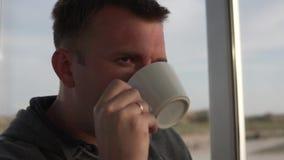 Ένας καφές κατανάλωσης ατόμων από ένα άσπρο φλυτζάνι E απόθεμα βίντεο