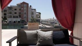 Ένας κενός καναπές και κυματισμός στις κουρτίνες αέρα σε έναν θερινό καφέ υπαίθρια απόθεμα βίντεο