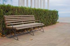 Ένας κενός ξύλινος πάγκος σε ένα πάρκο θαλασσίως Στοκ φωτογραφία με δικαίωμα ελεύθερης χρήσης