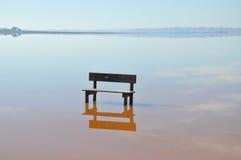 Ένας κενός πάγκος που στέκεται στη μέση του νερού ημέρα ηλιόλουστη Ήρεμο νερό Στοκ Φωτογραφίες
