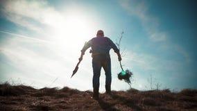 Ένας κηπουρός ατόμων με ένα φτυάρι της γης και τις ρίζες του οπωρωφόρου δέντρου, που φυτεύουν το χρόνο στην πλοκή κήπων Άνοιξη απόθεμα βίντεο