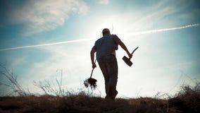 Ένας κηπουρός ατόμων με ένα φτυάρι της γης και τις ρίζες του οπωρωφόρου δέντρου, που φυτεύουν το χρόνο στην πλοκή κήπων o φιλμ μικρού μήκους