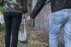 Ένας κλέφτης προσπαθεί να κλέψει μια τσάντα από πίσω στοκ εικόνες με δικαίωμα ελεύθερης χρήσης