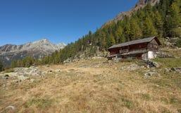 Ένας κλειστός σταύλος στην πτώση μπροστά από ένα λιβάδι βουνών στοκ εικόνες