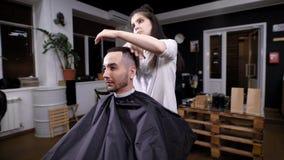 Ένας κομμωτής γυναικών ολοκληρώνει τον προσδιορισμό τρίχας για έναν επισκέπτη ενός barbershop, χρήσεις τρίχας στιλίστων ένα πήκτω απόθεμα βίντεο