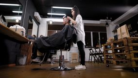 Ένας κομμωτής γυναικών ` s κτενίζει την τρίχα ενός επισκέπτη σε ένα barbershop, κατόπιν επιλέγει το κούρεμά του με trimmer απόθεμα βίντεο
