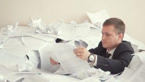 Ένας κουρασμένος υπάλληλος κάθεται σε έναν σωρό των εγγράφων Προβλήματα με την εργασία του υπαλλήλου Ένας νεαρός άνδρας σε ένα κο απόθεμα βίντεο