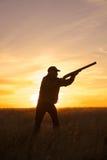 Κυνηγός με το κυνηγετικό όπλο επάνω στο ηλιοβασίλεμα Στοκ Εικόνες