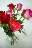 Ένας κόκκινος βαλεντίνος που τοποθετείται μεταξύ των τριαντάφυλλων σε ένα βάζο στοκ εικόνες