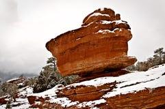 Ένας κόκκινος λίθος είναι ισορροπημένος σε ένα βουνό σε μια χιονώδη χειμερινή σκηνή στοκ εικόνα με δικαίωμα ελεύθερης χρήσης