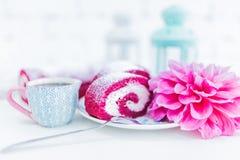 Ένας κόκκινος ρόλος κέικ βελούδου που τεμαχίζεται με το φλιτζάνι του καφέ ή το τσάι και τα λουλούδια Στοκ Εικόνα