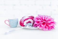 Ένας κόκκινος ρόλος κέικ βελούδου που τεμαχίζεται με το φλυτζάνι του γάλακτος και των λουλουδιών Στοκ εικόνες με δικαίωμα ελεύθερης χρήσης