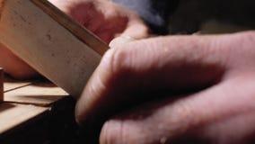 Ένας κύριος ξυλουργός αλέθει μια ξύλινη χτένα με το χέρι με να στρώσει με άμμο το έγγραφο κοντά επάνω 4 Κ φιλμ μικρού μήκους