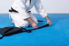 Ένας κύριος πολεμικών τεχνών με τη μαύρη ζώνη που διπλώνει το hakama του Στοκ φωτογραφία με δικαίωμα ελεύθερης χρήσης