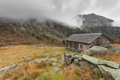 Ένας κλειστός σταύλος στην πτώση μπροστά από ένα λιβάδι βουνών στοκ φωτογραφίες
