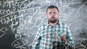 Ένας λαμπρός ώριμος μαθηματικός φέρνει έναν μεγάλο πίνακα και ολοκληρώνει ένα δοκίμιο περίπλοκη μαθηματική εξίσωση τύπου απόθεμα βίντεο