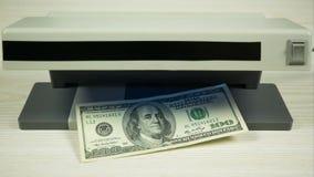 Ένας λογαριασμός εκατό-δολαρίων γίνομαι ένας-δολάριο κάτω από το υπεριώδες φως Κίνηση στάσεων φιλμ μικρού μήκους