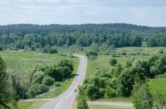 Ένας λοφώδης δρόμος σε μια θερινή ημέρα μέσω των τομέων, των λιβαδιών και των δασών Στοκ Εικόνες