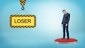 Ένας λυπημένος επιχειρηματίας στέκεται σε ένα μεγάλο κόκκινο κουμπί πλησίον σε ένα σημάδι κατασκευής με έναν γράφοντας ΗΤΤΗΜΕΝΟ Στοκ Εικόνες