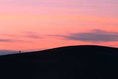 Ένας λόφος αμμόλοφων άμμου περπατήματος οδοιπόρων ηλιοβασιλέματος στοκ εικόνες