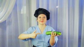 Ένας μάγειρας γυναικών σε μια ποδιά χαμογελά, κρατά ένα κολοκύθι κολοκυθιών στο χέρι της και δείχνει σε το απόθεμα βίντεο