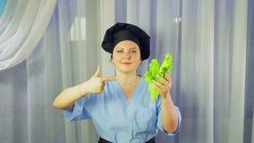 Ένας μάγειρας γυναικών σε μια ποδιά χαμογελά, κρατά μια πράσινη σαλάτα στο χέρι της και παρουσιάζει χέρι της σε το φιλμ μικρού μήκους