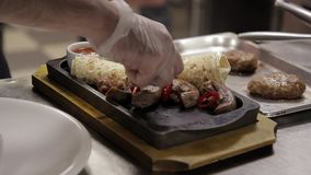 Ένας μάγειρας διακοσμεί ένα πιάτο με το ψωμί κρέατος και pita σε έναν δίσκο μετάλλων απόθεμα βίντεο