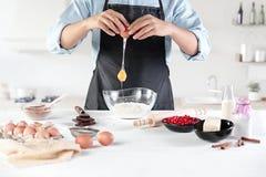 Ένας μάγειρας με τα αυγά σε μια αγροτική κουζίνα στα πλαίσια των χεριών ατόμων ` s Στοκ φωτογραφία με δικαίωμα ελεύθερης χρήσης