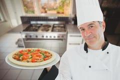 Ένας μάγειρας που φορά ένα καπέλο αρχιμαγείρων ` s κρατά μια πίτσα σε ένα πιάτο στο κλίμα κουζινών Στοκ φωτογραφία με δικαίωμα ελεύθερης χρήσης