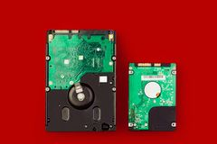 Ένας μεγάλος σκληρός δίσκος και ένα μικρό hdd σε ένα κόκκινο υπόβαθρο Στοκ φωτογραφία με δικαίωμα ελεύθερης χρήσης
