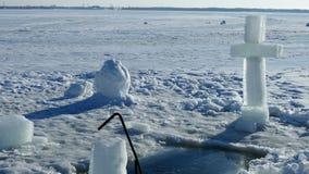 Ένας μεγάλος σταυρός μπροστά από μια πάγος-τρύπα Πριν από την ιεροτελεστία λουσίματος Θρησκευτική γιορτή Epiphany φιλμ μικρού μήκους