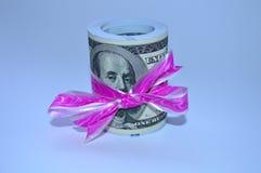 Ένας μεγάλος σωρός των δολαρίων έδεσε με μια ρόδινη κορδέλλα στοκ φωτογραφία