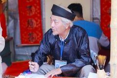 Ένας μελετητής γράφει τους κινεζικούς χαρακτήρες καλλιγραφίας στο ναό της λογοτεχνίας Στοκ εικόνες με δικαίωμα ελεύθερης χρήσης