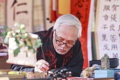 Ένας μελετητής γράφει τους κινεζικούς χαρακτήρες καλλιγραφίας στο ναό της λογοτεχνίας Στοκ Φωτογραφίες