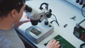 Ένας μηχανικός βάζει την ασύρματη ενότητα WI-Fi πρόσβασης στην περιοχή με ένα μικροσκόπιο απόθεμα βίντεο