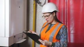 Ένας μηχανικός γυναικών ελέγχει τις παραμέτρους του συστήματος θέρμανσης Ο μηχανικός στο κράνος γράφει κάτω τις αναγνώσεις οργάνω απόθεμα βίντεο