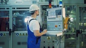 Ένας μηχανικός διαχειρίζεται την πλαστικός-παραγωγή του εξοπλισμού μέσω του πίνακα ελέγχου φιλμ μικρού μήκους