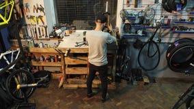 Ένας μηχανικός ποδηλάτων ατόμων με μια γενειάδα συγκεντρώνει ένα ποδήλατο βουνών στο εργαστήριό του φιλμ μικρού μήκους