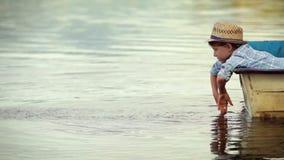 Ένας μικρός δανδής έχει τον καλύτερο χρόνο που χαλαρώνει στη βάρκα στη μέση μιας λίμνης απόθεμα βίντεο