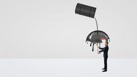 Ένας μικρός επιχειρηματίας που κρύβει κάτω από μια ομπρέλα από τη διαρροή αργού πετρελαίου ενός μεγάλου μαύρου βαρελιού Στοκ εικόνα με δικαίωμα ελεύθερης χρήσης