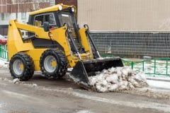 Ένας μικρός κίτρινος εκσακαφέας καθαρίζει την οδό από το χιόνι στοκ εικόνα